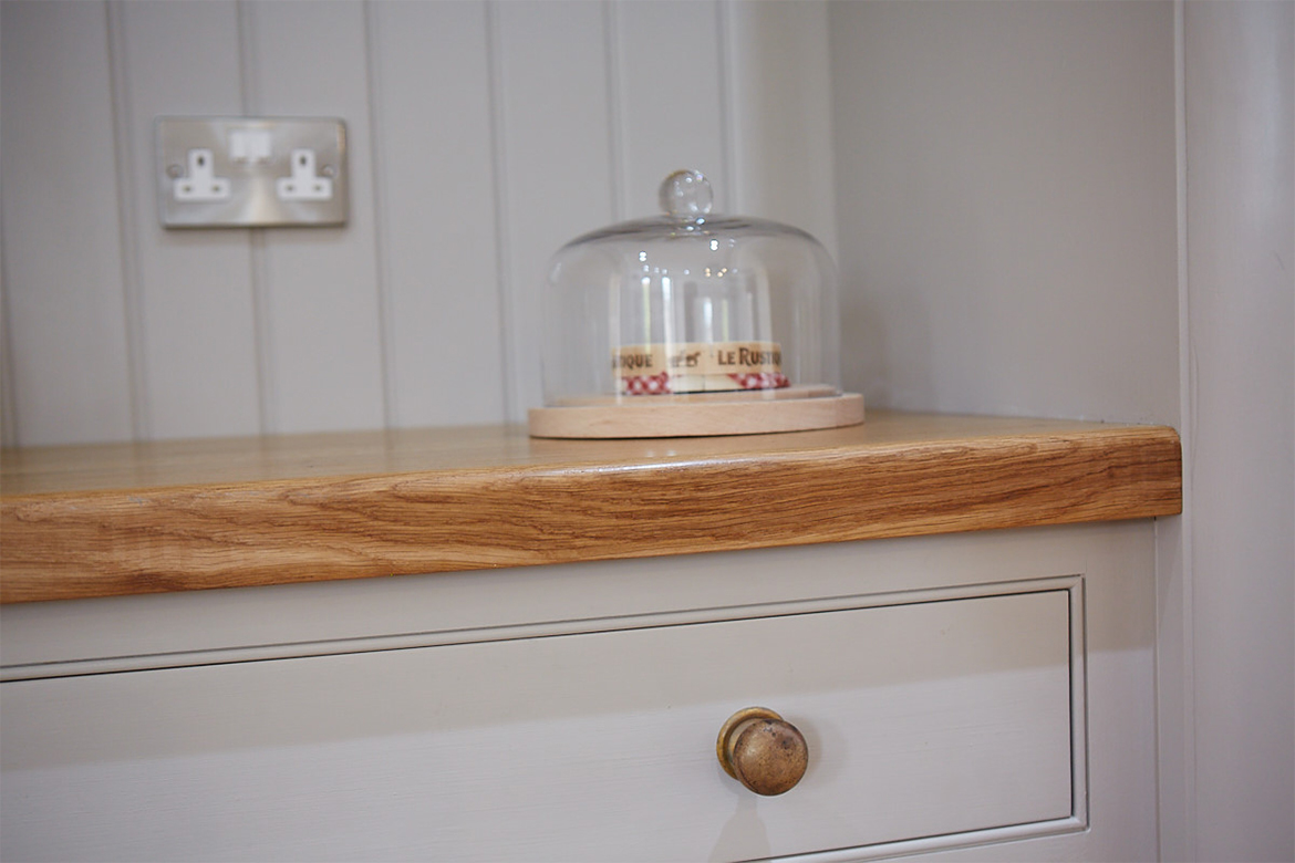 Glass cake cover sits on top of painted kitchen cabinets with solid oak worktop