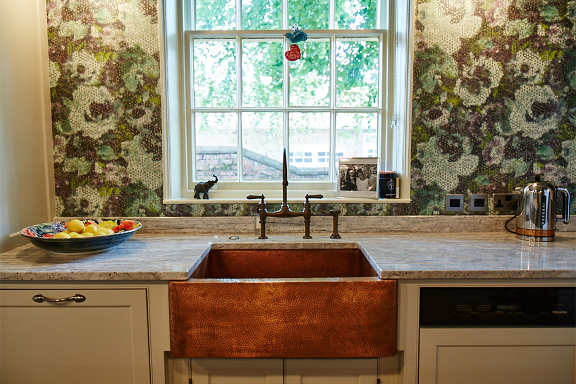 Beaten copper belfast sink with antique copper bridge taps set in front of window with green floral wallpaper