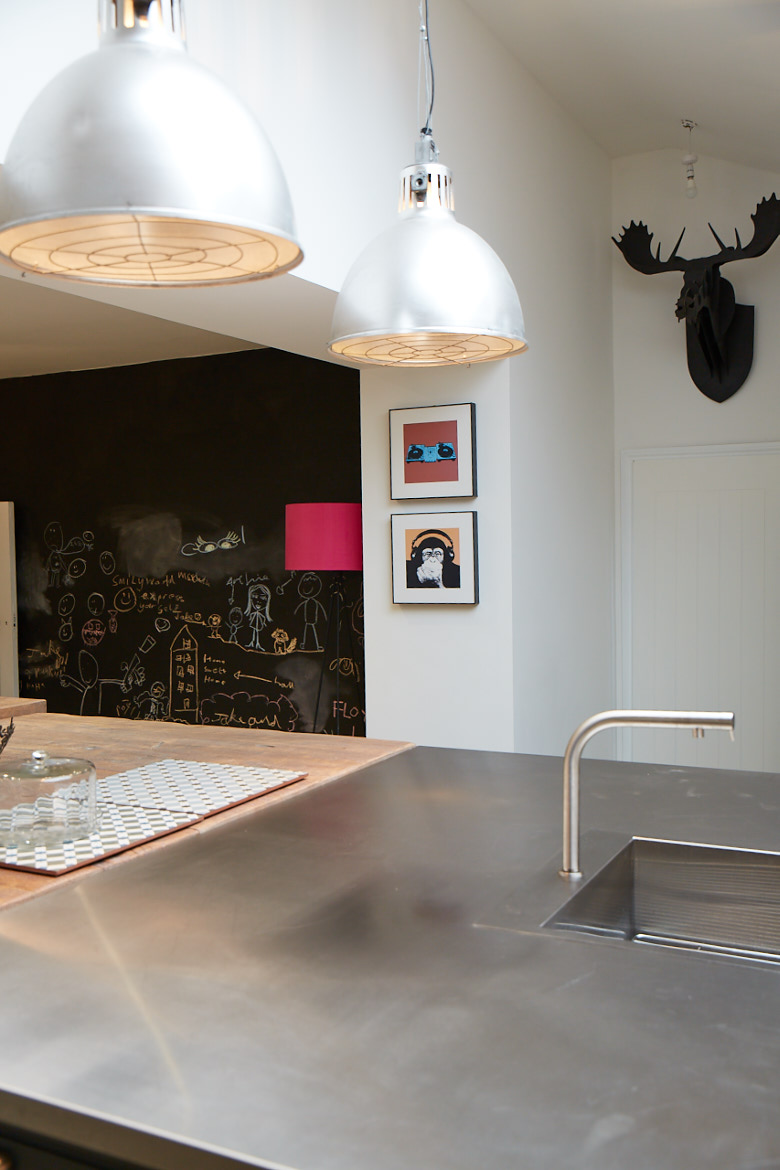 Bespoke stainless steel kitchen island worktop with large stainless pendant lighting above and black stag in background
