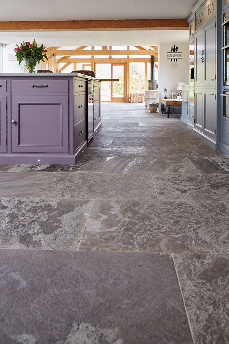 Bespoke purple kitchen island sits on grey stone floor tiles