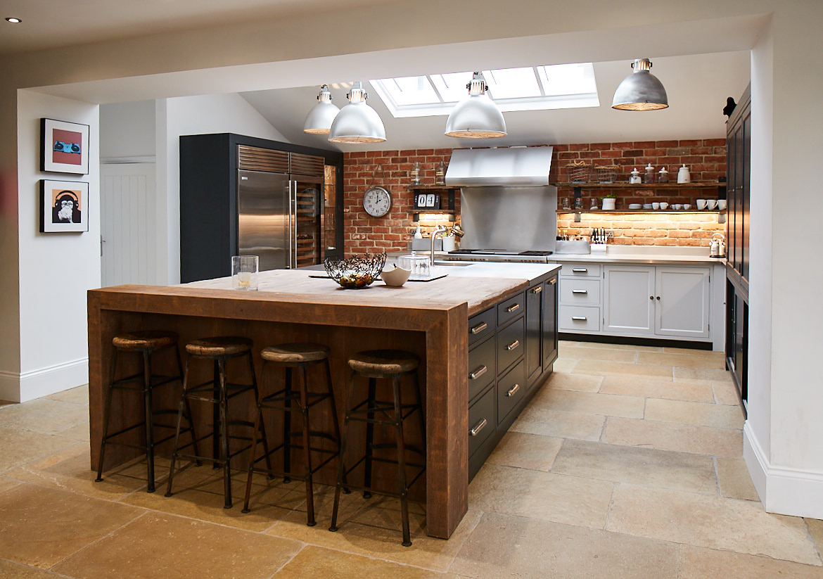 Wide shot of full kitchen by The Main Company including exposed brick wall bespoke painted island and reclaimed oak breakfast bar with complementing stools