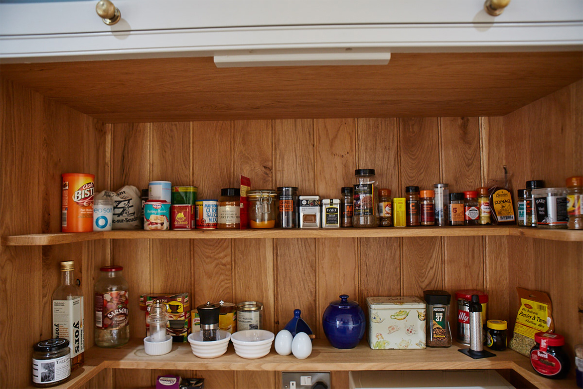 Wrap around larder gallery shelves displaying herbs and spices against solid oak backboards