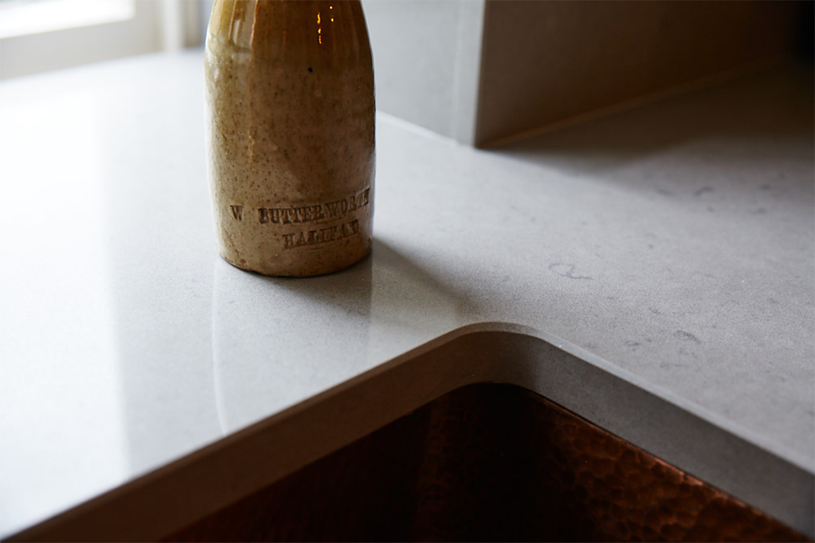 Bottle sat on bespoke grey caesarstone quartz worktops