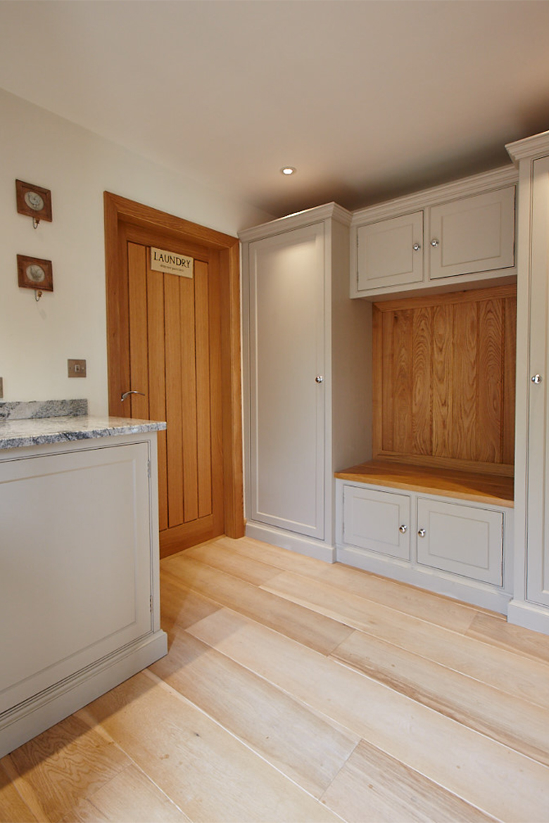 Solid oak laundry door with bespoke painted cabinets and boot cupboard