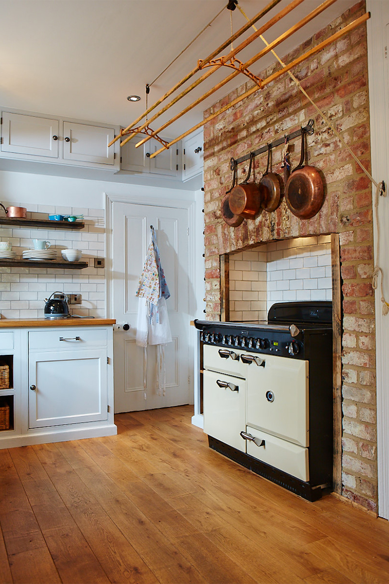 Cream range cooker in exposed brick chimney breast and hanging copper pans