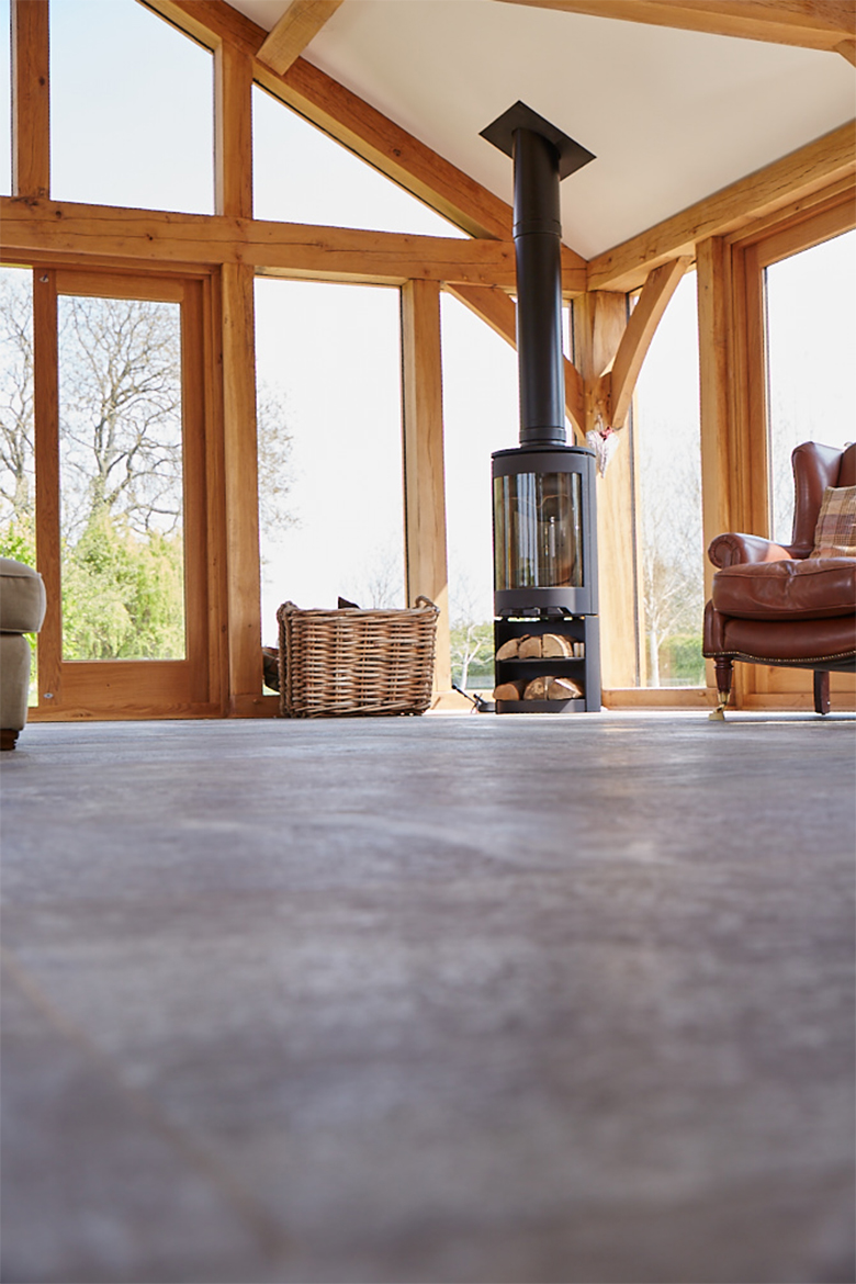 Open log burner sits on grey stone tile floor in oak beam house