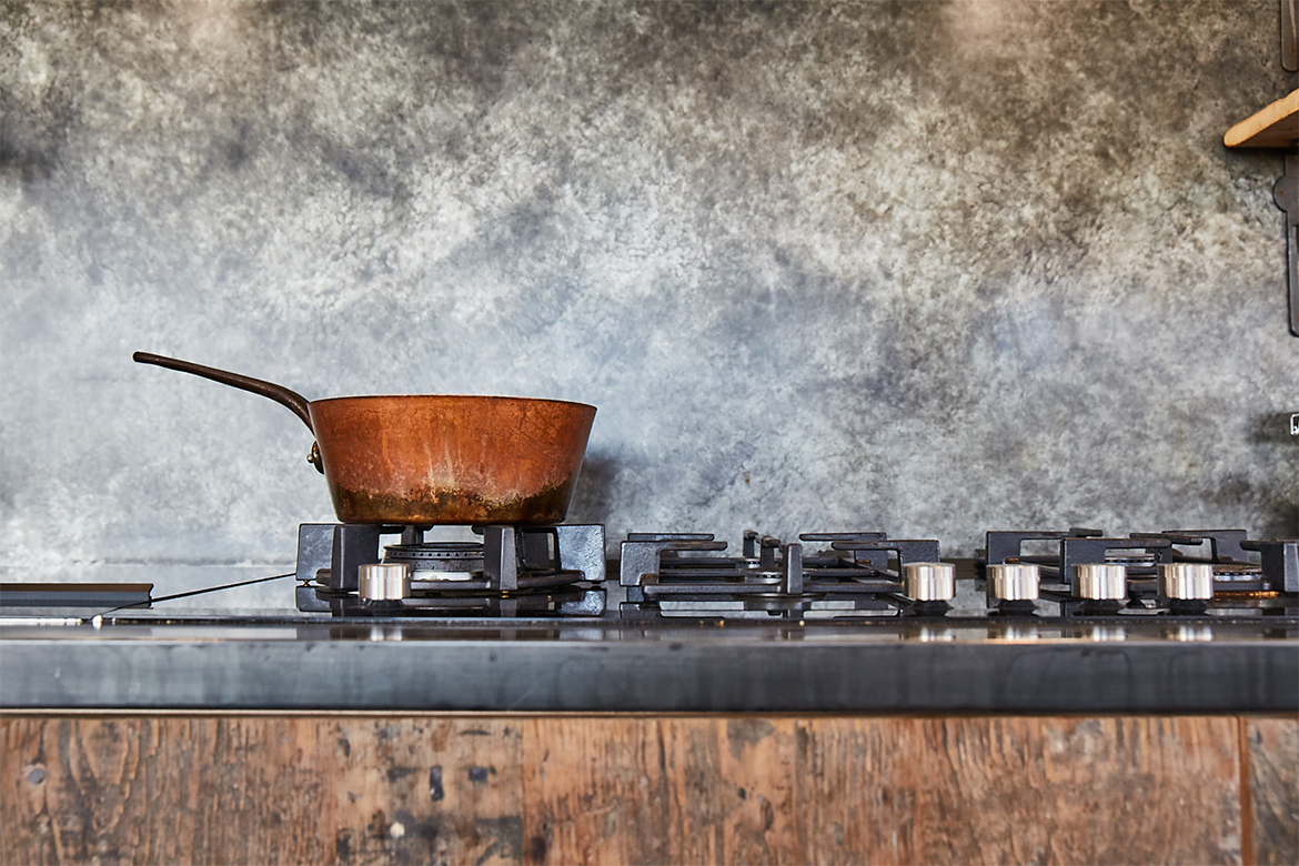 Copper pan sits on bespoke kitchen units with zinc patina worktop and matching backsplash