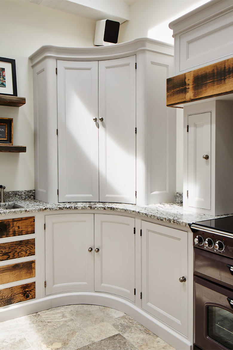 Curved kitchen cabinets with granite worktop and pewter handles