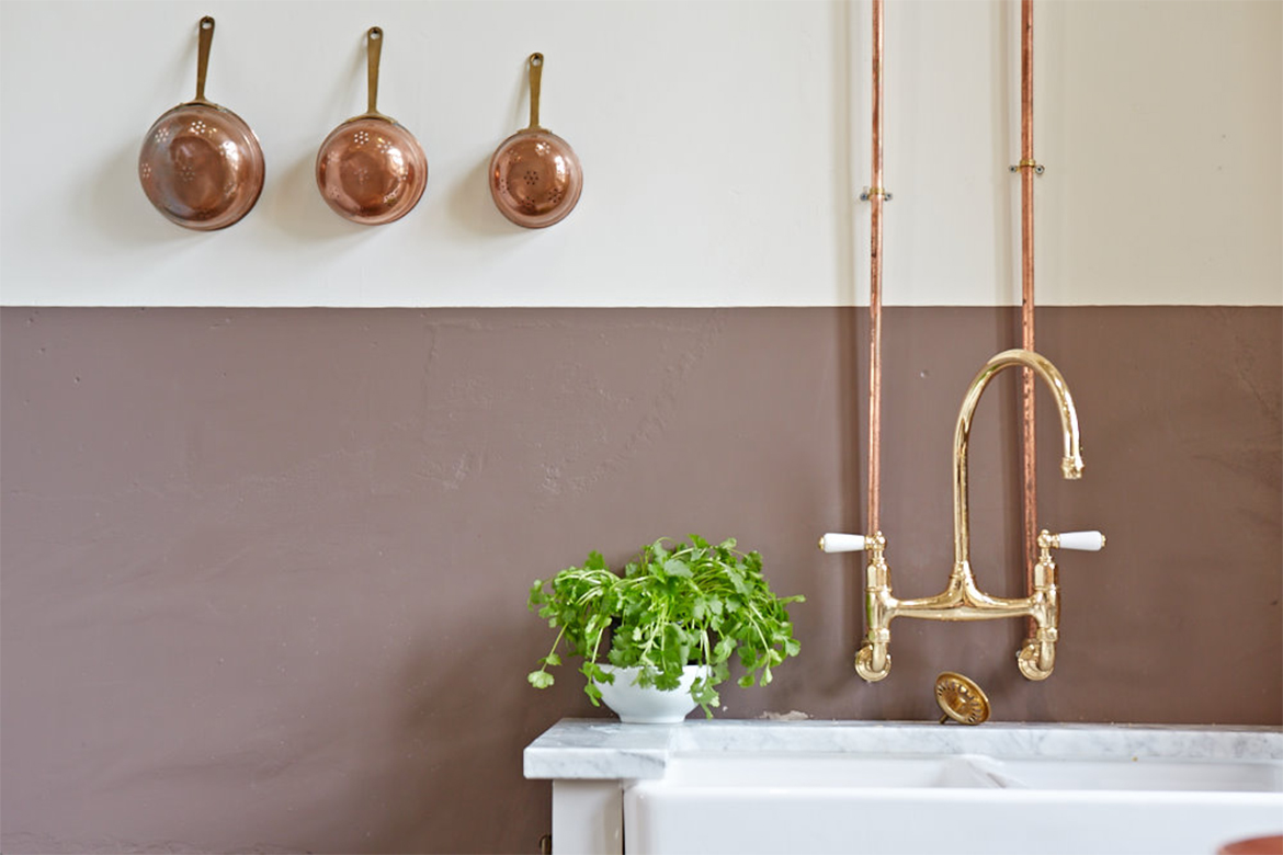 Exposed copper pipes and pans against painted white wall