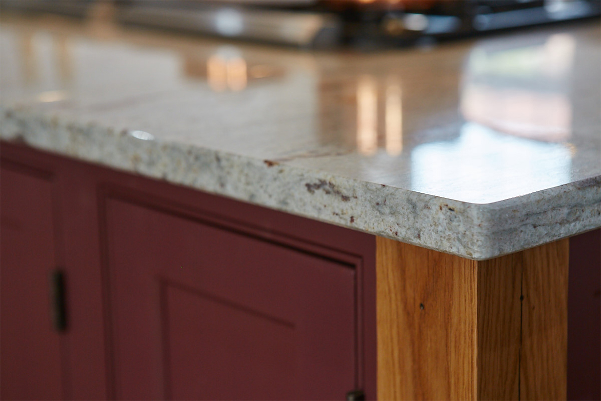 Close up of granite, oak leg and painted plum colour of kitchen cabinets