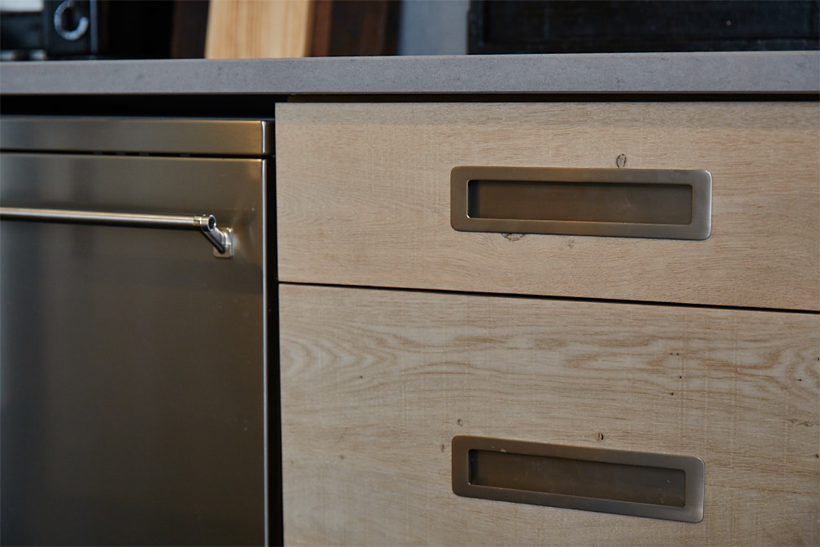 Inset brushed kitchen handles against the bespoke oak engineered pan drawer