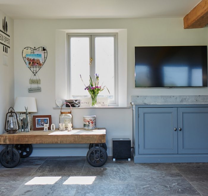 Reclaimed oak wood cart sits in front of window with traditional painted bespoke kitchen cabinets