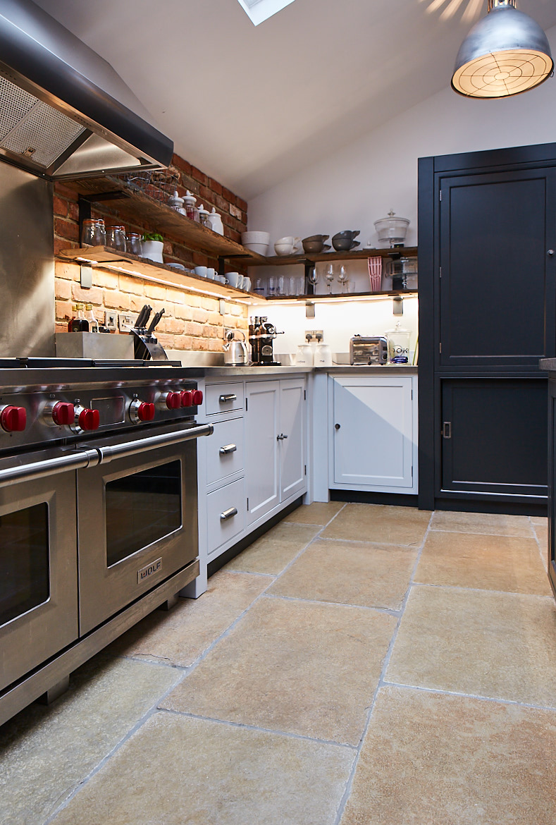 Wolf range cooker and painted bespoke cabinetry set against an exposed brick wall