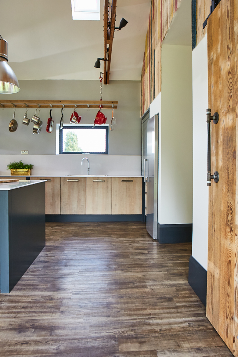 Rustic bespoke kitchen units with integrated stainless steel sink and pans hanging above