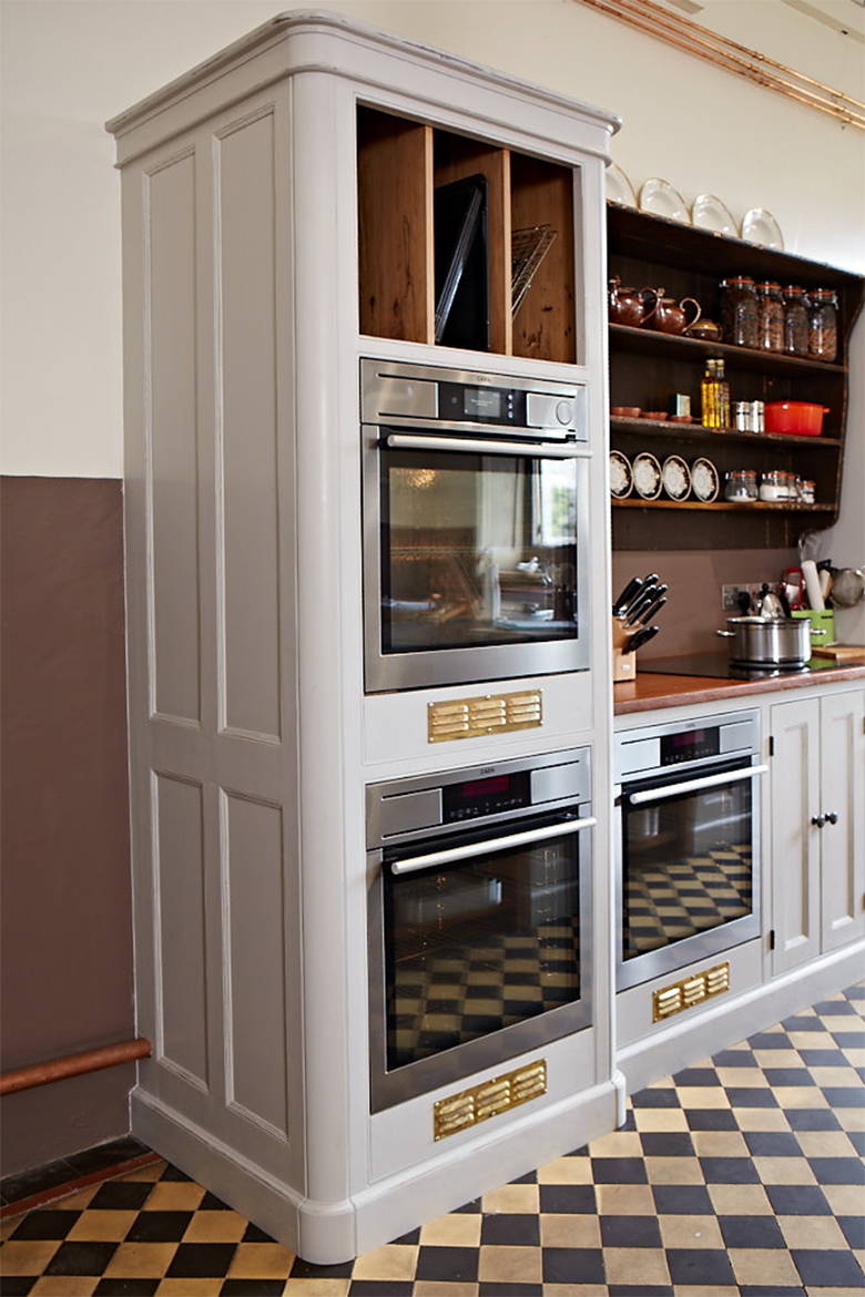 Eye level ovens in painted kitchen cabinets and gold grills