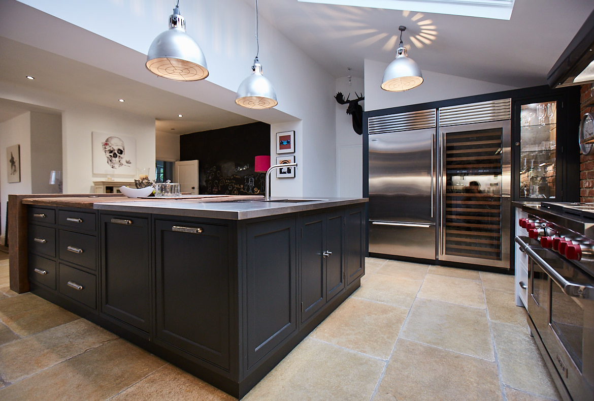 Front of bespoke kitchen island painted in a deep blue to contrast the stainless steel wine fridge and light walls