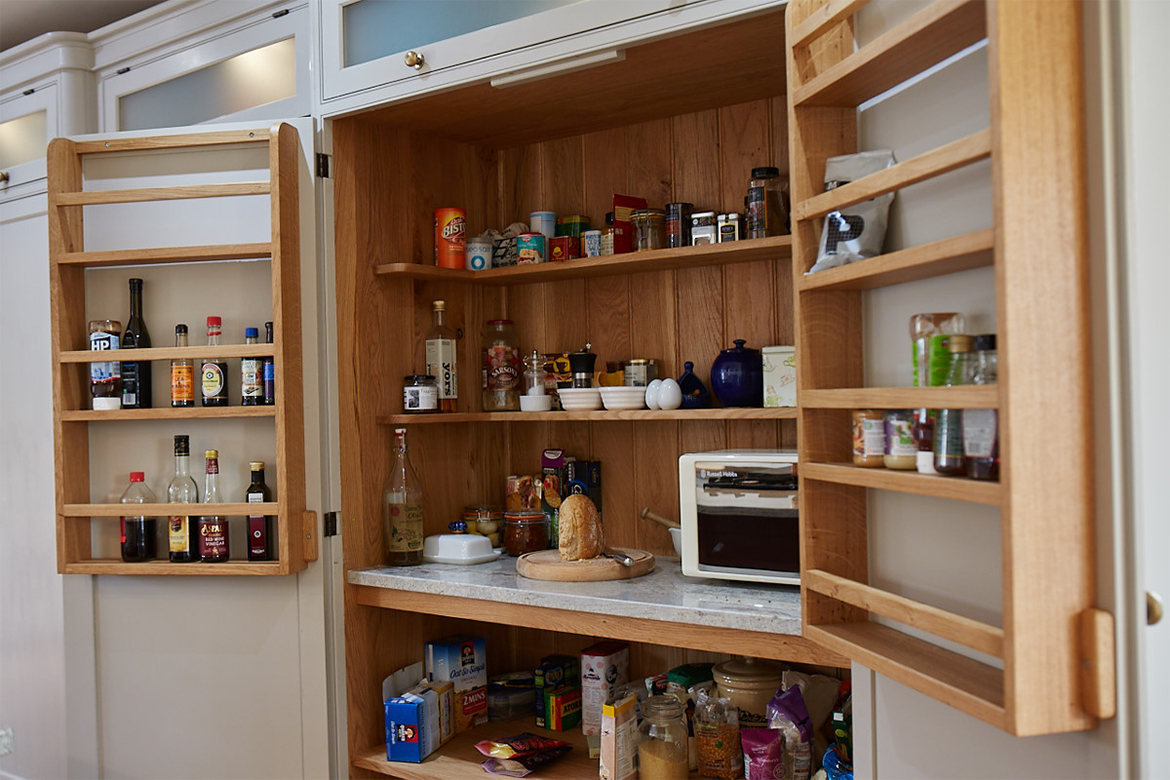 Internals of solid oak larder with freestanding microwave sat on granite and oak shelves full with food