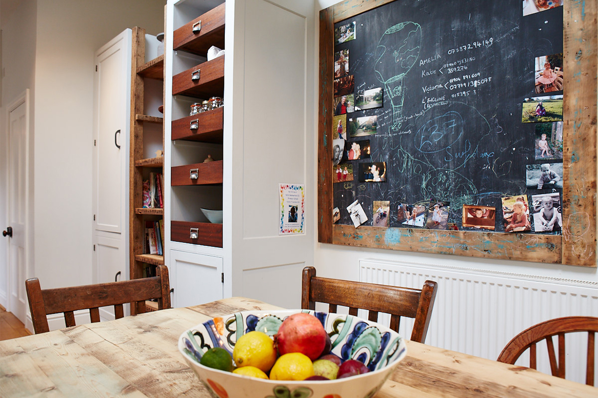 Tall bespoke kitchen cabinets with blackboard and fresh fruit on reclaimed wood table