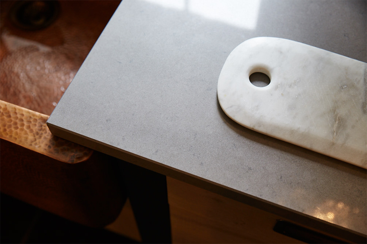 Marble chopping board rests on bespoke quartz grey caesarstone worktops
