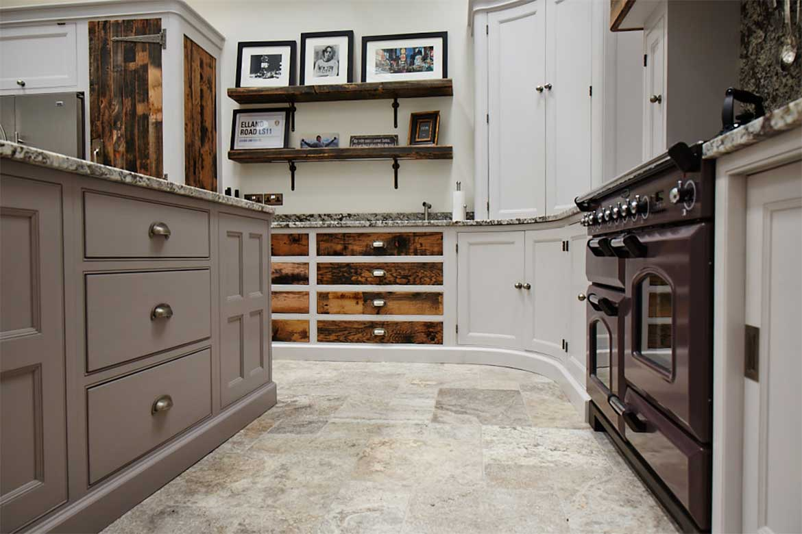 A deep purple range cooker sits alongside reclaimed oak drawer fronts with painted frames