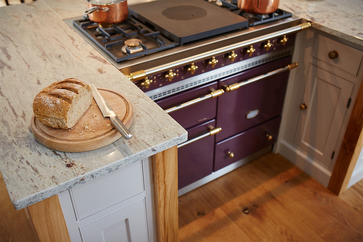 Plum lacanche range cooker sat in between two bespoke painted kitchen cabinets with solid oak legs