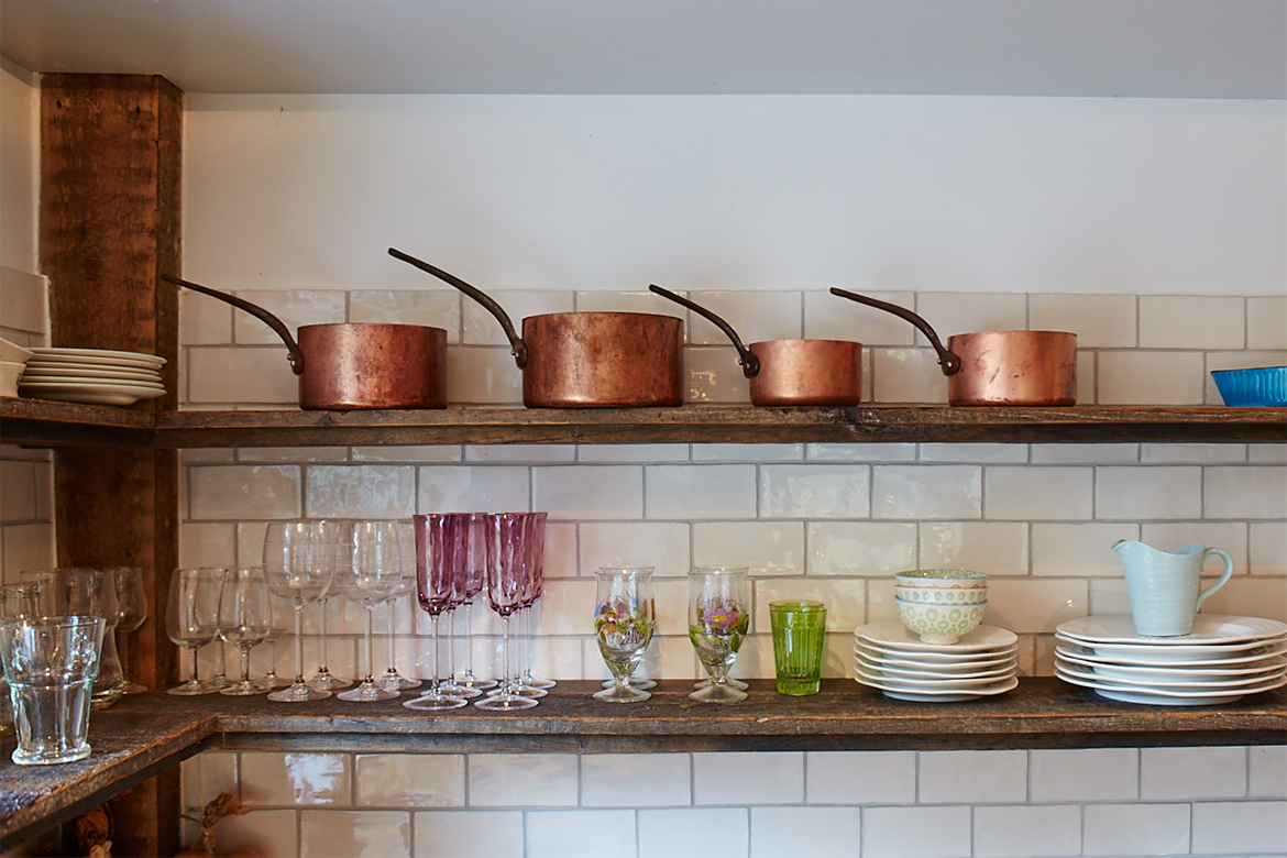 Reclaimed oak shelves against white metro tiles with copper pans