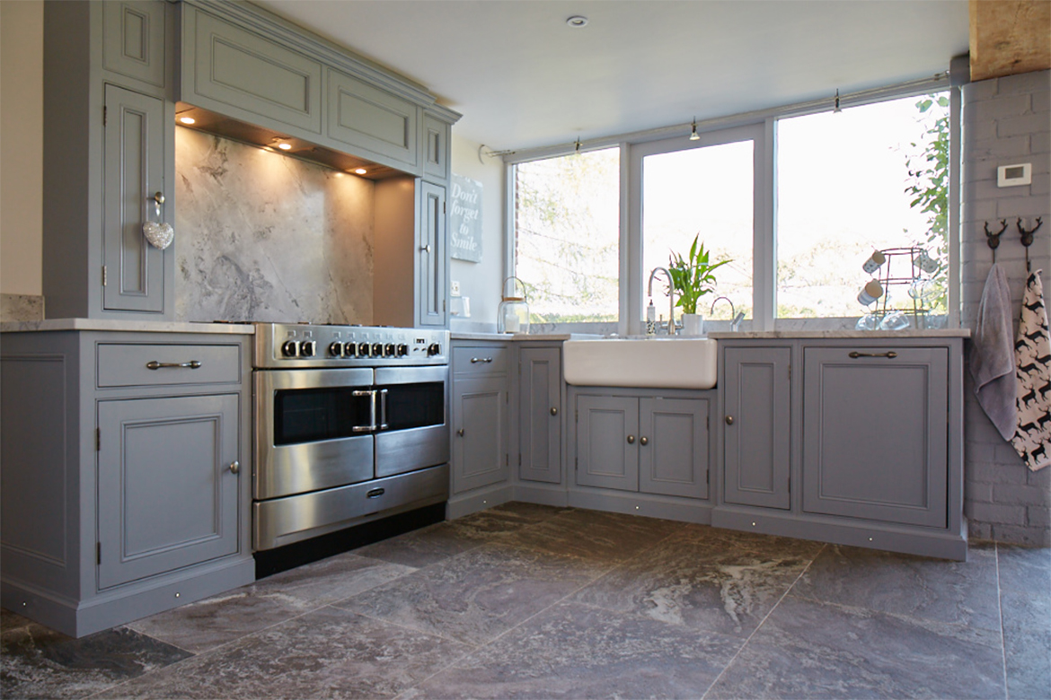 Traditional painted bespoke mantle over stainless steel range cooker with ceramic belfast sink in l shape configuration