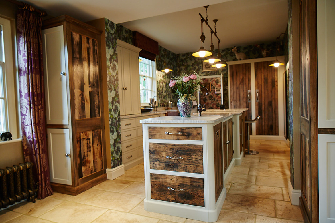 Reclaimed and painted bespoke kitchens cabinets sat on light stone floor with reclaimed oak drawer fronts in foreground