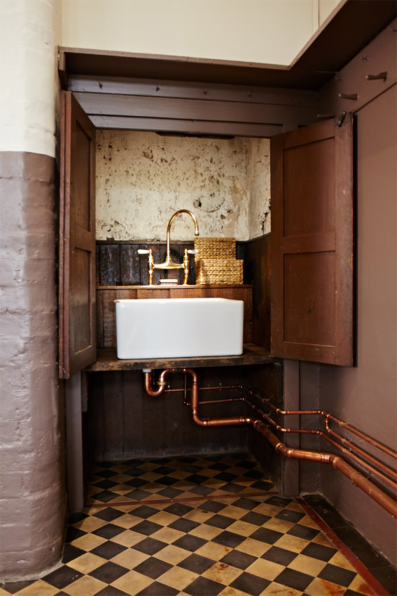Ceramic sink in pantry cupboard with exposed copper pipes