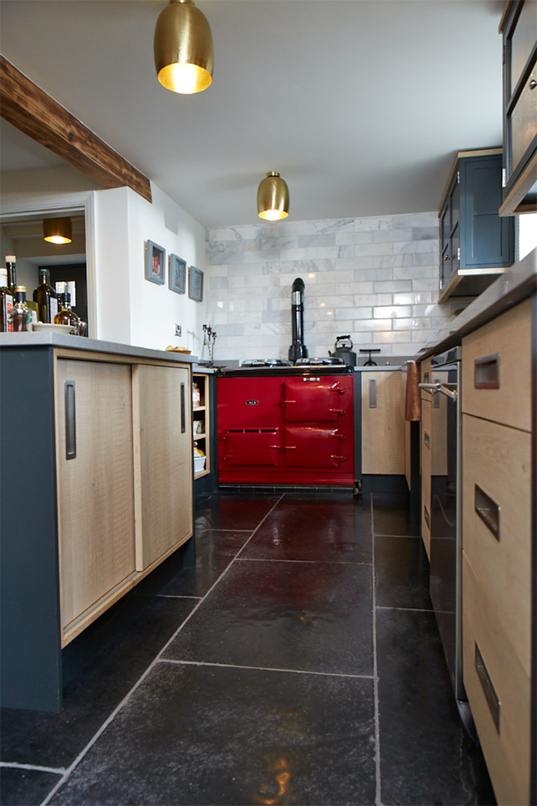 Red Aga and bespoke oak kitchen units with painted little green posts and caesarstone worktops