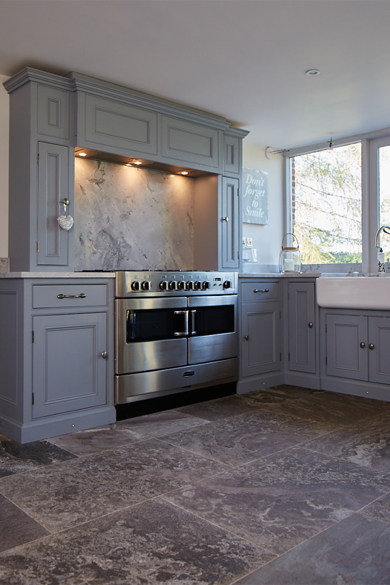 Stainless steel oven sits within bespoke painted kitchen cabinets on mantle housing extractor