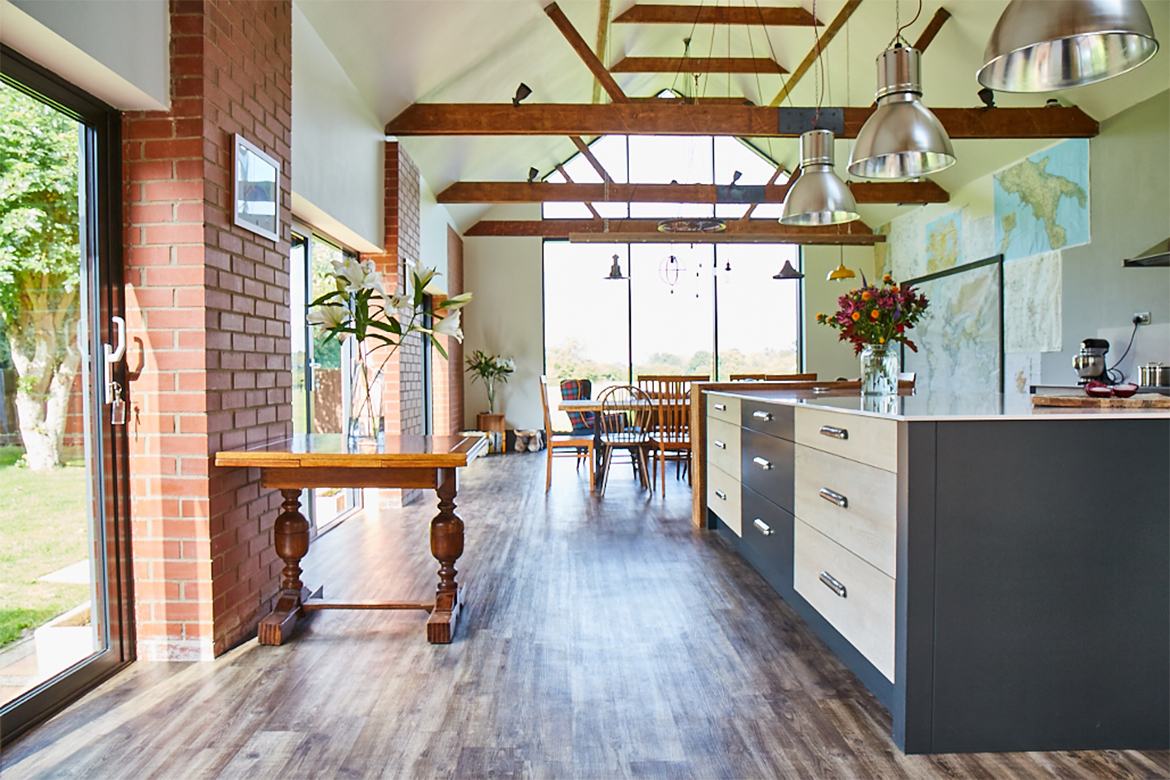 High vaulted room with bespoke kitchen island and antique table