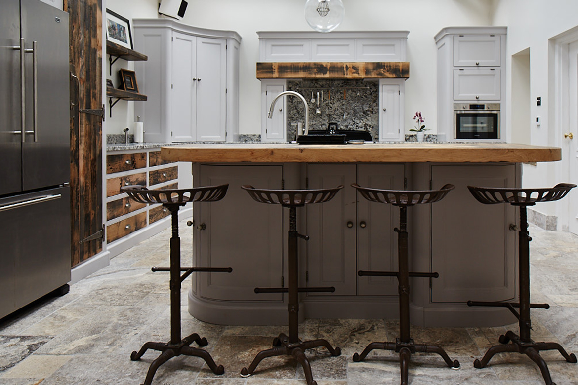 4 Cast iron bar stools sit under the thick reclaimed oak breakfast bar