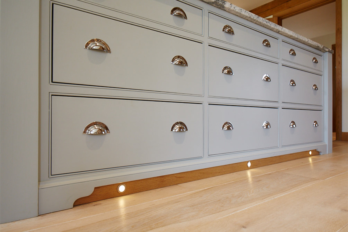 Close up of solid oak plinth with lights and chrome cup handles on drawer fronts