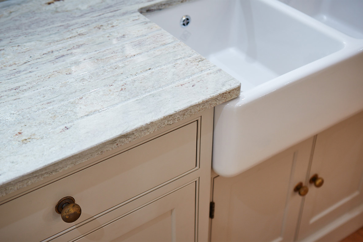 Close up detail of shaws double belfast sink with granite worktops and painted kitchen cabinets with burnt brass knobs