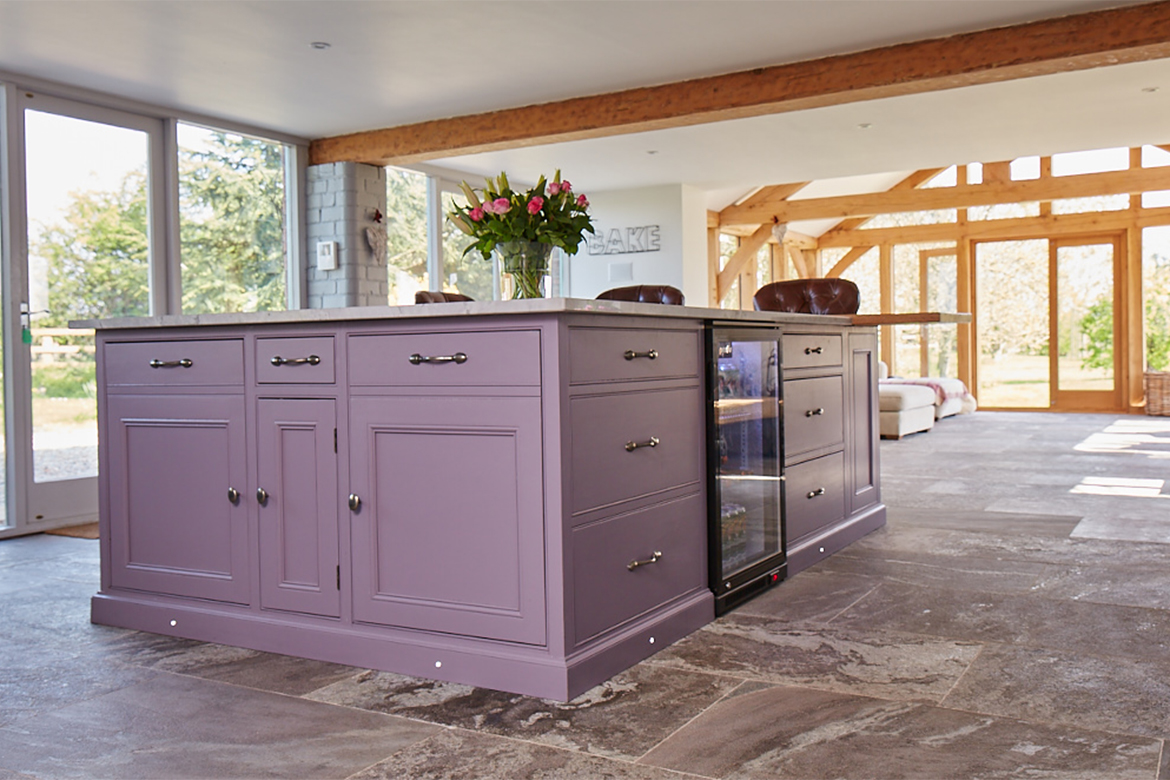 Bespoke purple kitchen island with freestanding wine cooler and plinth lights