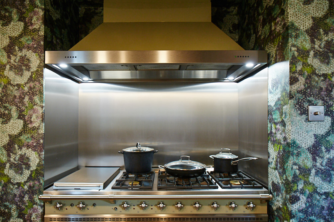 Green Chaussin Lacanche range cooker sat in alcove with colourful wall paper and stainless steel backsplash