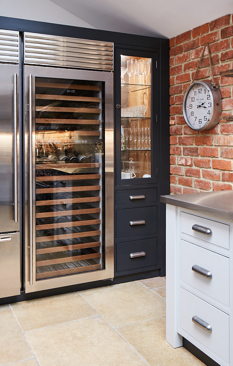 Full height Wolf stainless steel wine fridge next to a bespoke glazed cabinet
