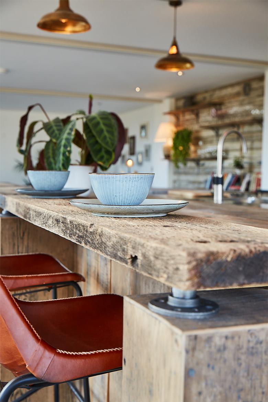 Chunky reclaimed oak rustic breakfast bar with blue mug and saucer