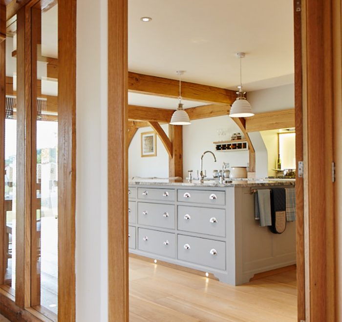 View of the painted kitchen island with granite worktop through solid oak architecture frame