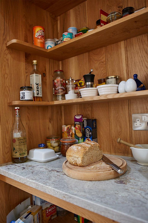 Bread and food being prepared inside bespoke oak larder cupboard with granite worktop and wrap around shelves