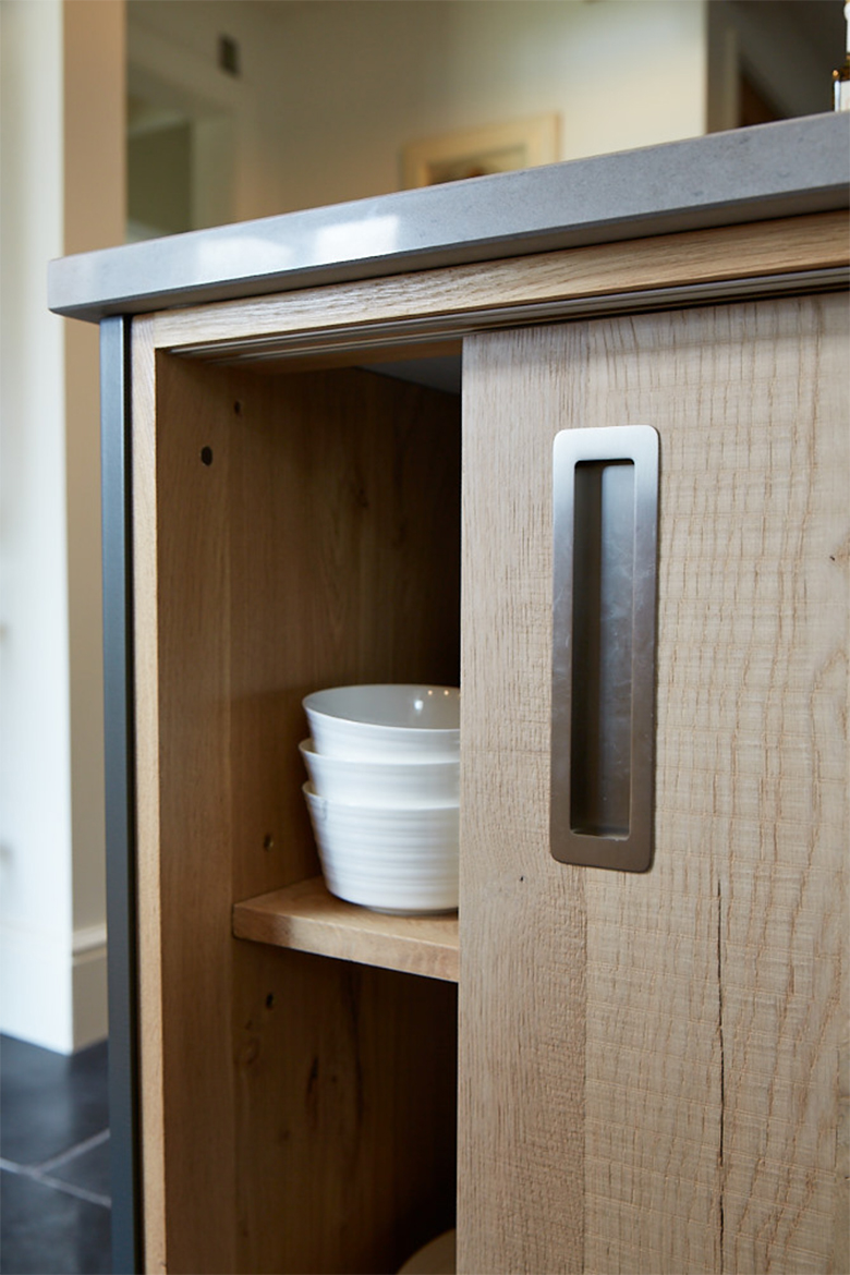Porcelain bowls in bespoke oak sliding door kitchen cabinet with inset handle