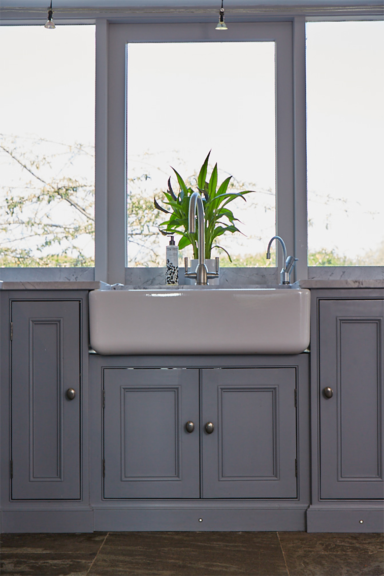 Shaws ceramic double belfast sink and brushed nickel tap sits on painted bespoke cabinet