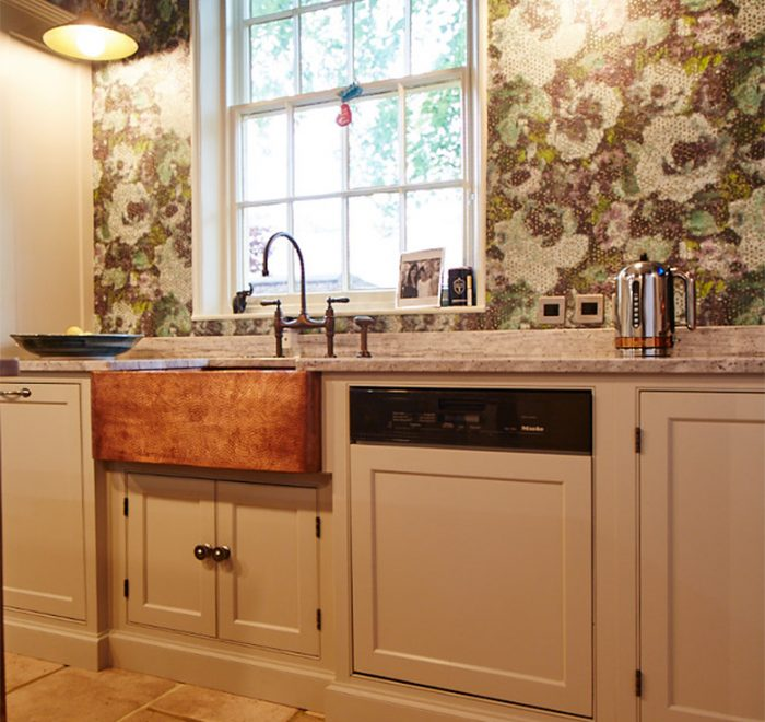 Bespoke painted kitchen run in Little Greene with integrated Miele dishwasher and beaten copper belfast sink with colourful green wallpaper