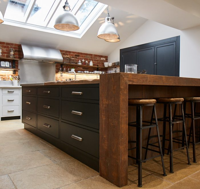 Bespoke kitchen island with chunky reclaimed oak breakfast bar wrap around and a stainless steel worktop