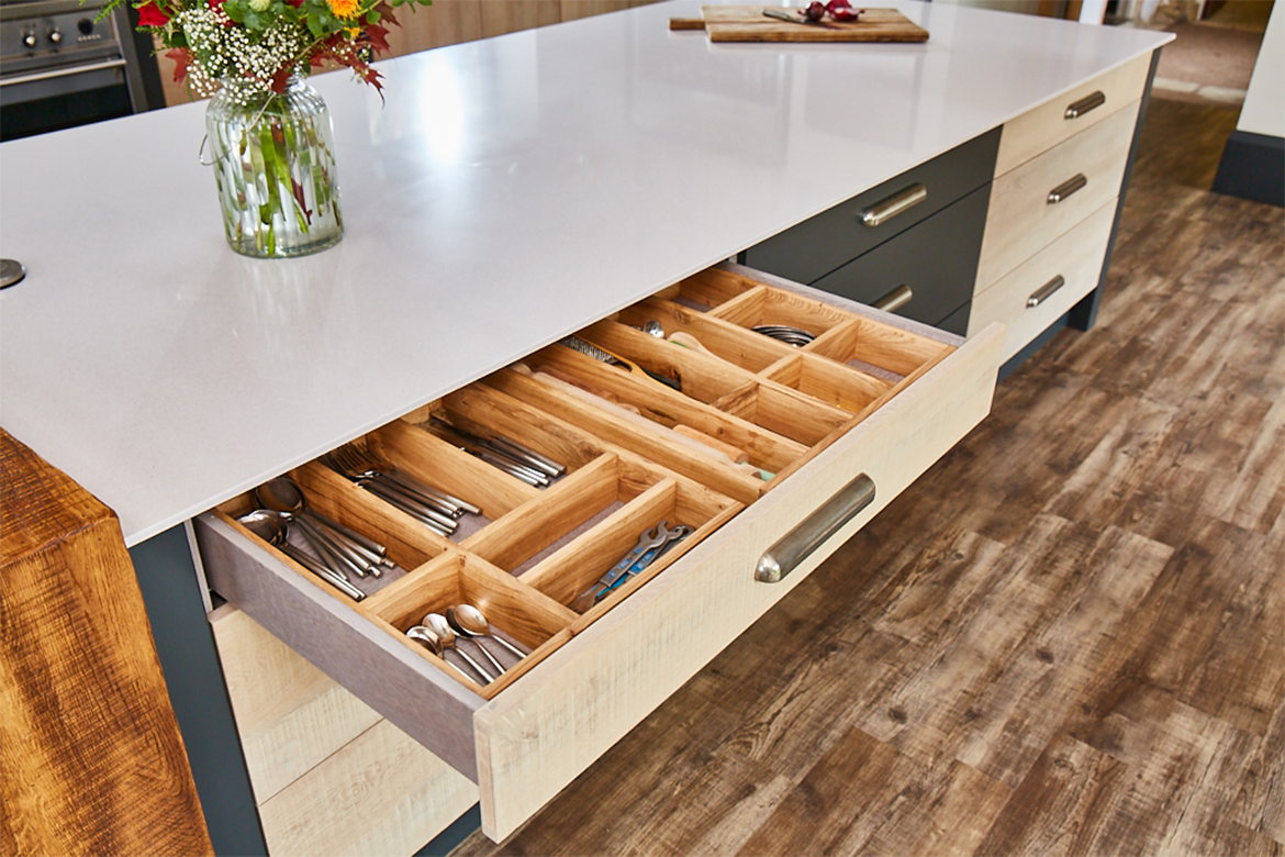 Bespoke kitchen drawer open with solid oak wood cutlery divider and dekton worktop