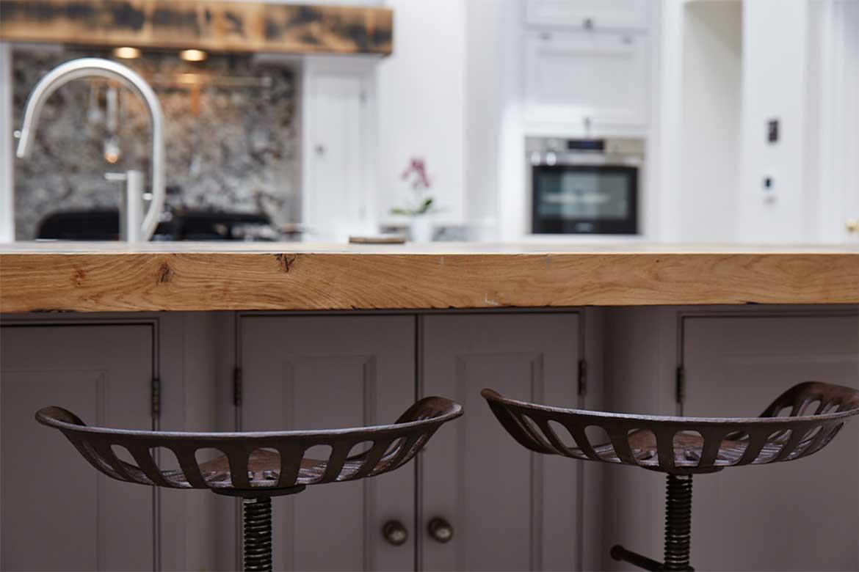 Cast iron stools under reclaimed oak breakfast bar