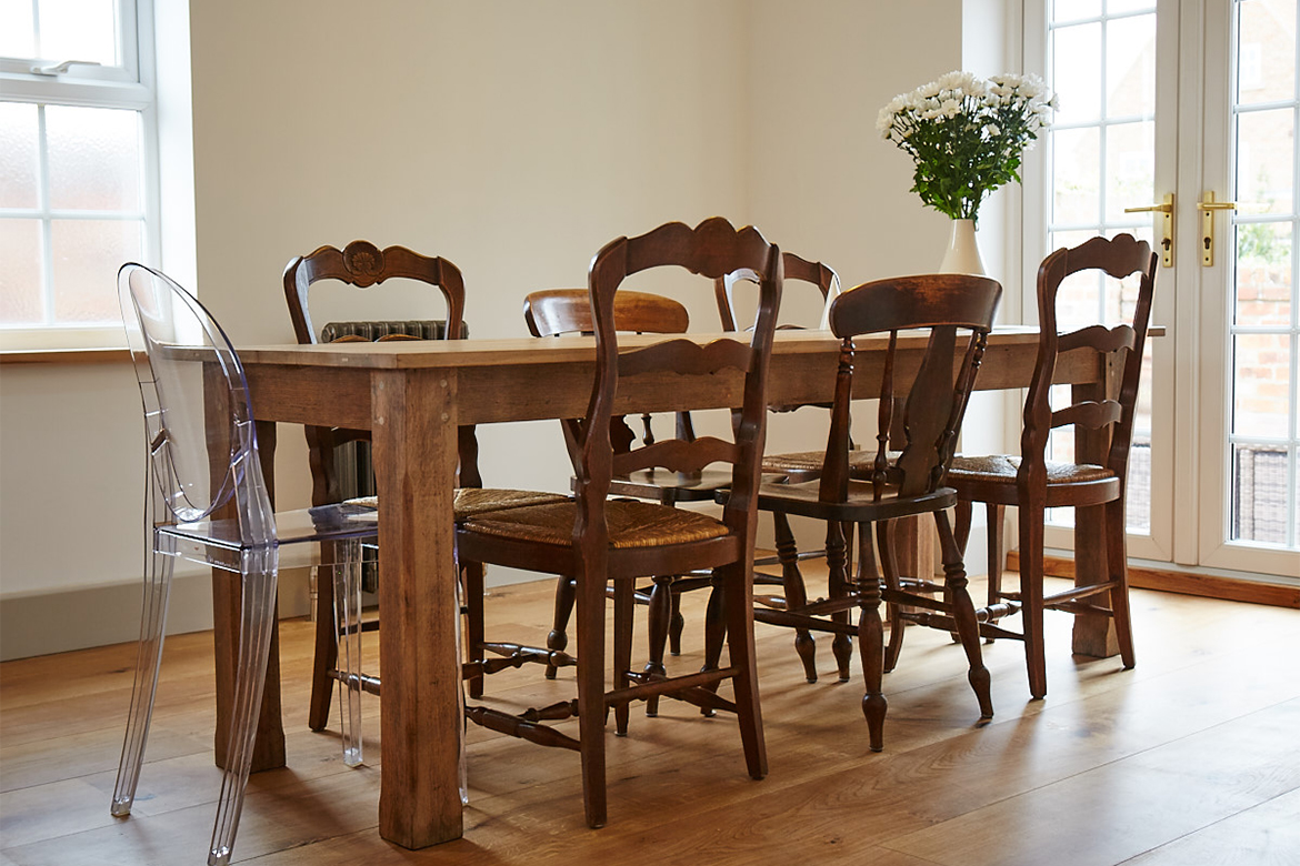 Reclaimed kitchen dining table with eclectic mix of dining chairs