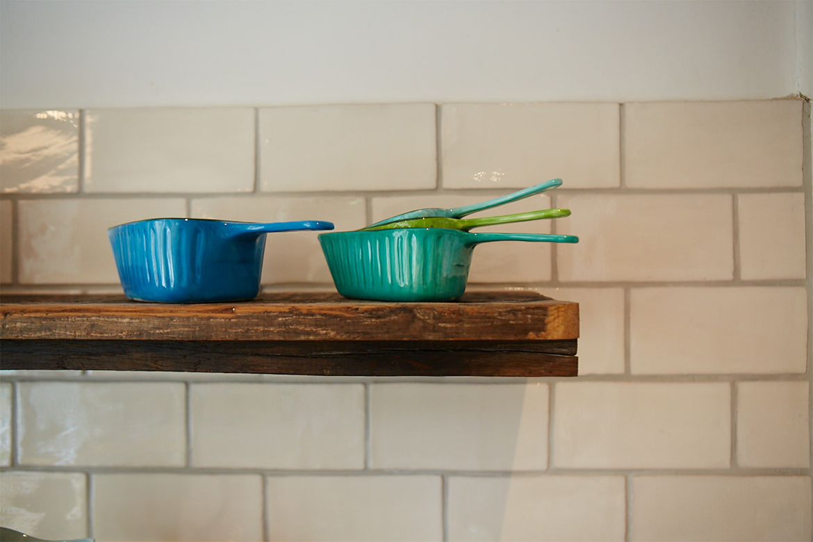 Colourful bowls on reclaimed oak shelves against white metro tiles