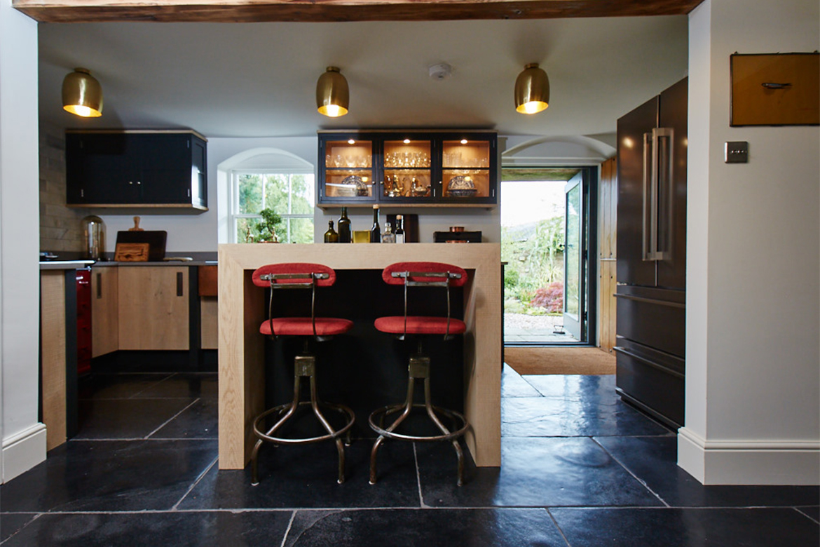 Red bar stools under bespoke oak breakfast bar wrap around